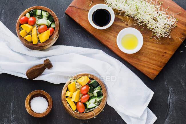 Colocación plana de cuencos de madera rellenos de microgreens y rematada con calabacín crudo y calabazas con tomate cherry en la superficie de pizarra - foto de stock