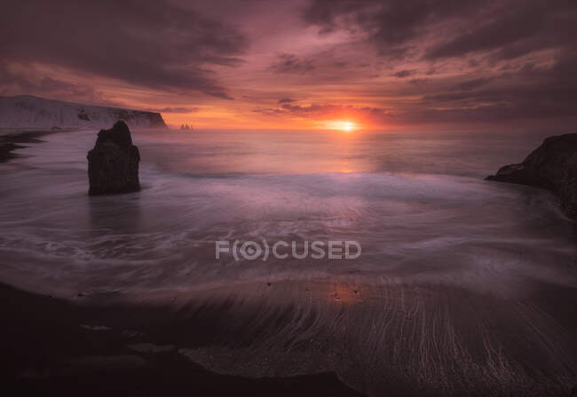 Spectacular natural scenery of rough frozen coast with foamy waves under cloudy sky during beautiful sunset in Iceland — Stock Photo