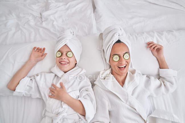 Сверху счастливая молодая женщина и ребенок, одетые в белые халаты и полотенца тюрбаны лежащие на кровати с огуречными ломтиками на глазах и смеющиеся, веселясь и наслаждаясь процедурой красоты дома — стоковое фото
