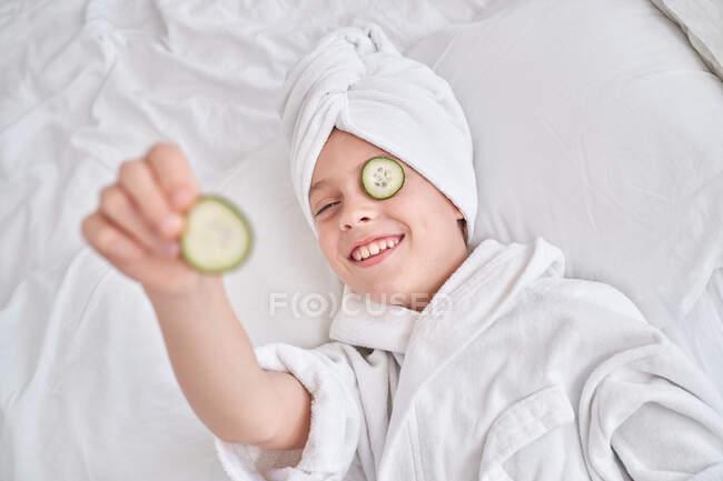 Niño feliz disfrutando de procedimiento de belleza - foto de stock