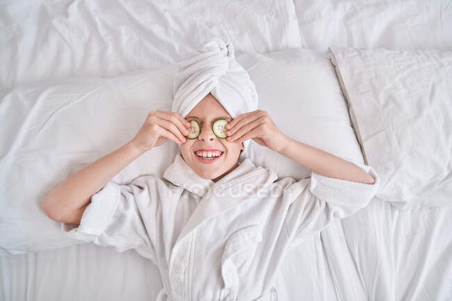 Cheerful kid with slices of cucumber on yes lying on bed — Stock Photo