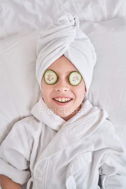 Веселый ребенок с кусками огурца на да лежит на кровати — стоковое фото