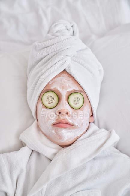 Verspieltes Kind mit Gesichtsmaske auf Bett liegend — Stockfoto