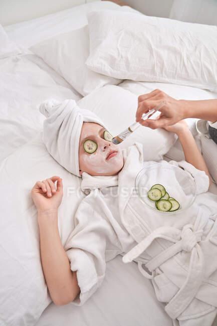 Женщина надевает маску на лицо ребенка — стоковое фото