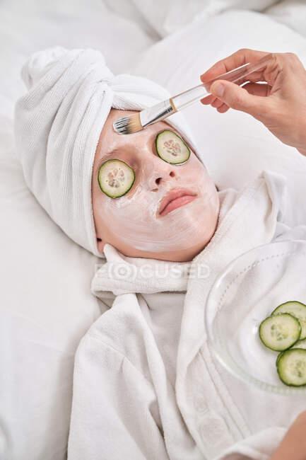 Frau trägt Maske auf Gesicht von Kind auf — Stockfoto
