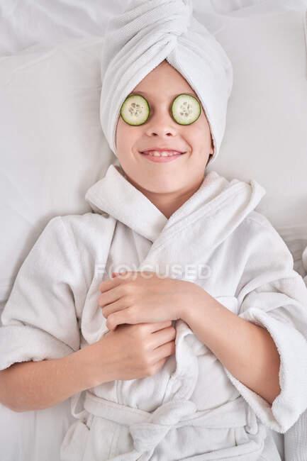 Alegre niño con rodajas de pepino en sí acostado en la cama - foto de stock