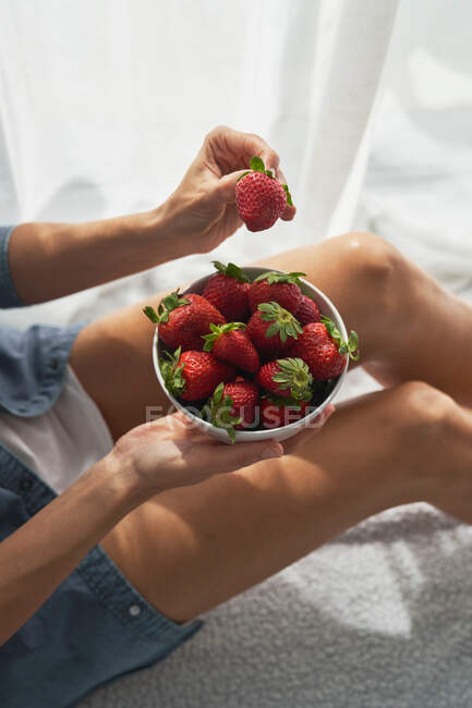From above anonymous female demonstrating bowl of ripe strawberries while sitting on bed at home on summer day — Stock Photo