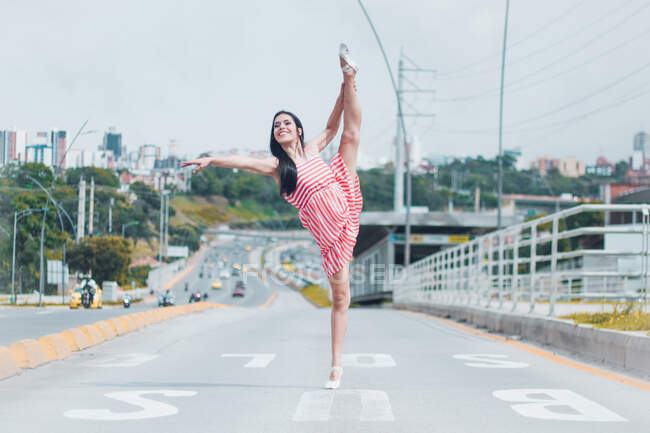 Full body young ballerina smiling and doing splits on empty lane of road while dancing in modern city outskirts — Stock Photo