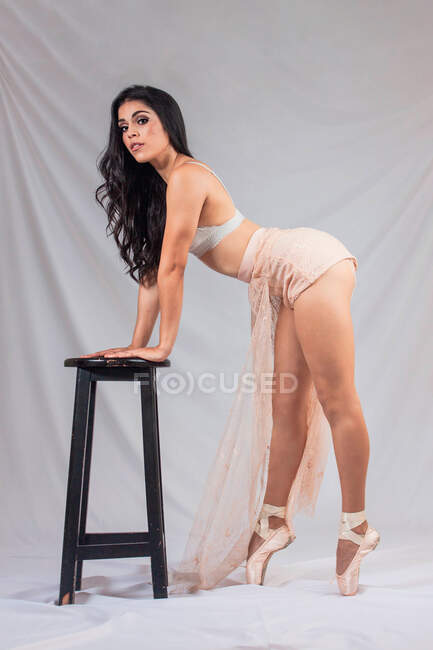Side view of woman in white bra and translucent skirt leaning on stool and looking at camera while dancing against gray background — Stock Photo