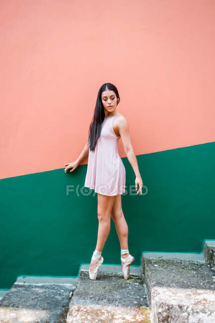 Ballerina with closed eyes in pointe shoes standing on tip of toes on weathered steps while dancing against striped colorful wall on street — Stock Photo