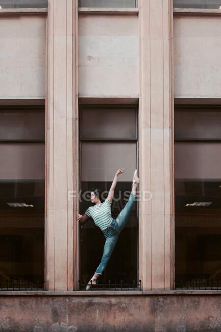 Longitud completa mujer delgada en ropa casual haciendo splits mientras se estira y baila fuera del edificio resistido en la ciudad - foto de stock