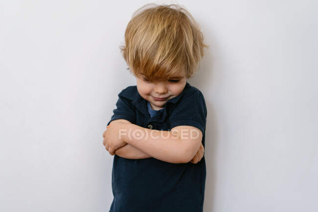 Niño rubio molesto con ropa casual mirando hacia abajo con insatisfacción mientras está de pie en la pared blanca con los brazos cruzados - foto de stock