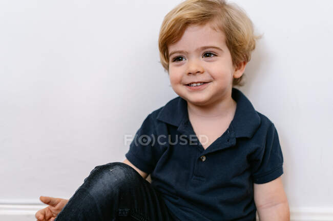 Adorable preschool boy in casual tee shirt smiling looking away sitting and leaning in a white wall background — Stock Photo