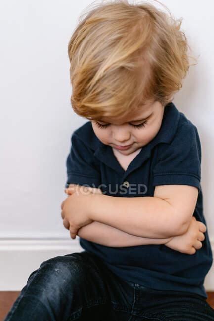 Niño rubio molesto con ropa casual sentado en el suelo con los brazos cruzados - foto de stock
