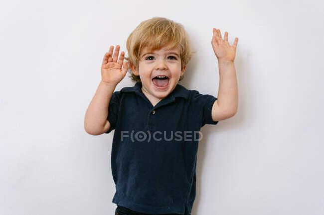 Menino pré-escolar adorável em camiseta casual rindo da câmera enquanto levanta as mãos e se prepara para jogos de dedo encostados em um fundo de parede branca — Fotografia de Stock