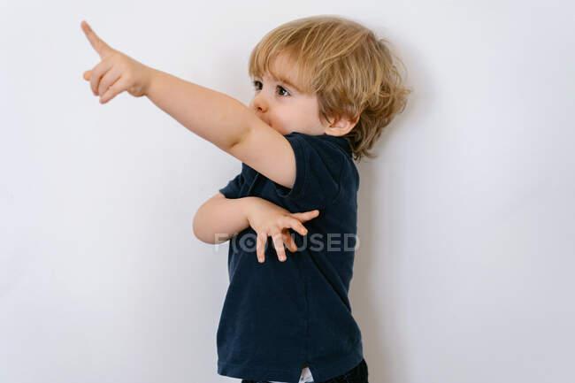 Adorable niño preescolar con camiseta casual mirando hacia otro lado mientras levanta el brazo jugando juegos con los dedos apoyados en un fondo blanco de la pared - foto de stock