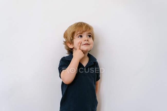 Очаровательный дошкольник в футболке, отводящий взгляд, указывая пальцем в лицо, наклоняясь на белом фоне. — стоковое фото