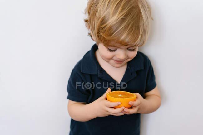 Petit garçon blond drôle en vêtements décontractés mangeant la moitié de l'orange en regardant loin avec le sourire tout en se tenant sur fond blanc — Photo de stock