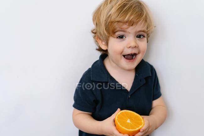 Engraçado menino loiro em roupas casuais comendo metade de laranja olhando para longe com o sorriso enquanto em pé contra o fundo branco — Fotografia de Stock