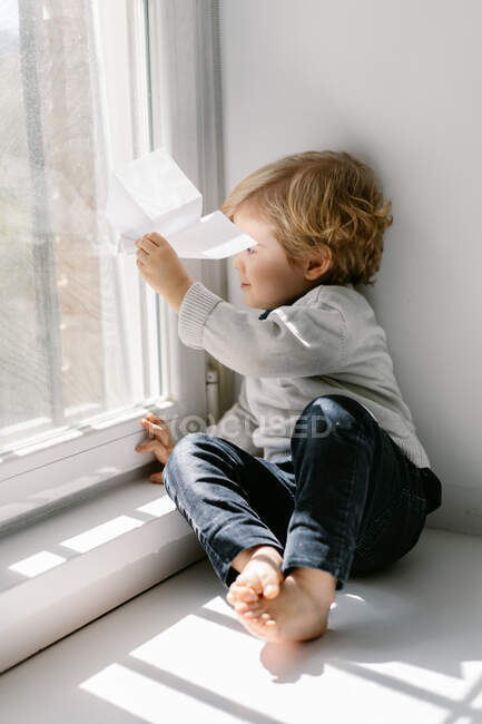 Side view of blonde little child in casual clothes playing with paper airplane while sitting barefoot on window sill on sunny day — Stock Photo