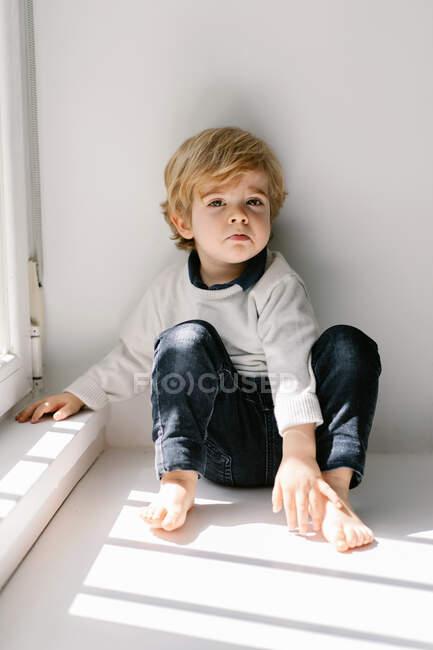 Niño rubio molesto mirando a la cámara con insatisfacción mientras está sentado en el alféizar apoyado en la pared blanca - foto de stock