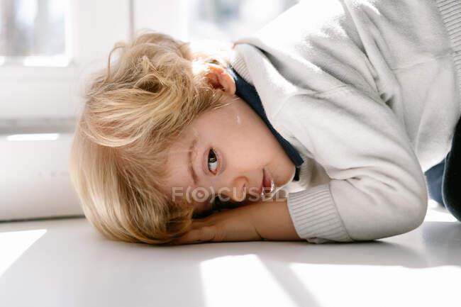 Vista lateral del tranquilo chico rubio en ropa casual mirando a la cámara mientras descansa en el alféizar de la ventana en un apartamento moderno en un día soleado - foto de stock