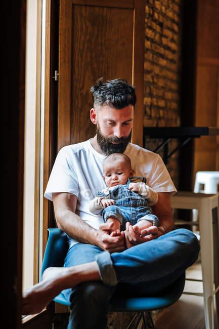 Bearded father with baby sitting near window — Stock Photo