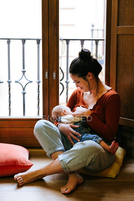 Happy mother breastfeeding baby near window — Stock Photo
