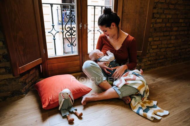 Bonne mère allaitant bébé près de la fenêtre — Photo de stock