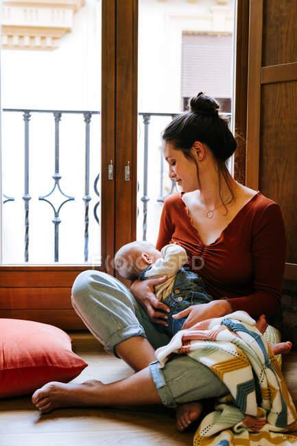 Glückliche Mutter stillt Baby am Fenster — Stockfoto