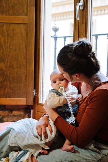 Мать с ребенком сидит у окна — стоковое фото