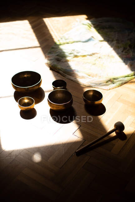 From above collection of traditional tibetan bowls and striker placed in sunlight on wooden floor in dark room — Stock Photo