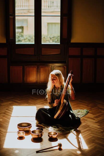 Frau spielt Leier in der Nähe tibetischer Schalen — Stockfoto