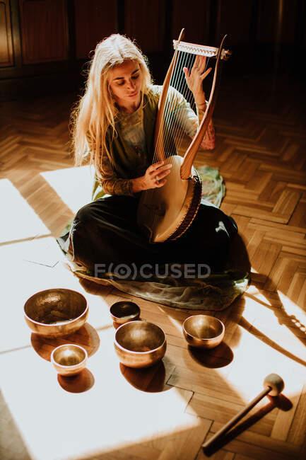 Hohe Winkel der blonden Frau sitzt auf dem Boden in der Nähe tibetischer Schalen und spielt Leier in gemütlichen Raum zu Hause — Stockfoto