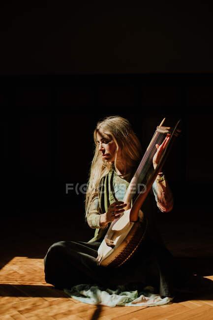 Frau spielt Leier im dunklen Raum — Stockfoto
