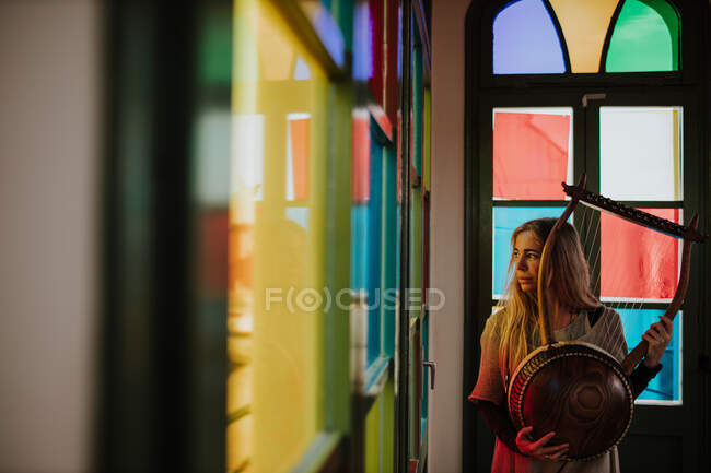 Adult female musician with lyre looking out window while standing in room decorated with colorful stained glass — Stock Photo