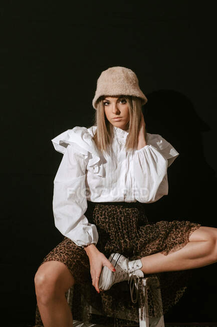 Молодая женщина в модном наряде касается волос и смотрит в камеру, сидя на черном фоне — стоковое фото