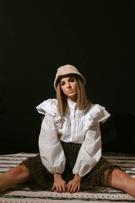 Молодая милая блондинка в стильном наряде и шляпе сидит на полу и улыбается для камеры на черном фоне — стоковое фото
