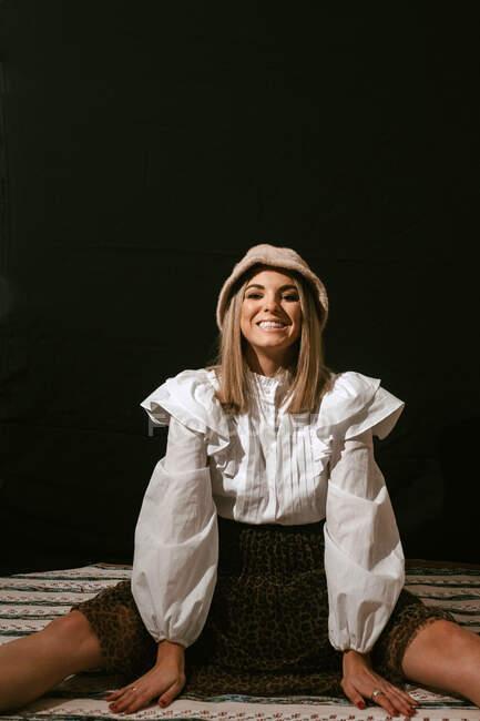 Веселая молодая симпатичная блондинка в стильном наряде и шляпе сидит на полу и улыбается для камеры на черном фоне — стоковое фото