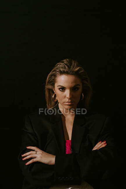 Giovane donna bionda con le braccia incrociate in elegante giacca tuta nera guardando la fotocamera sullo sfondo nero — Foto stock