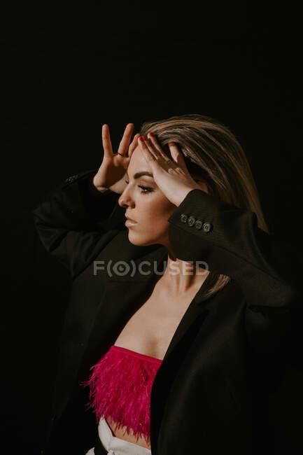 Vue latérale de la jeune femme blonde dans une veste élégante et un haut de culture touchant les cheveux et regardant loin sur fond noir — Photo de stock