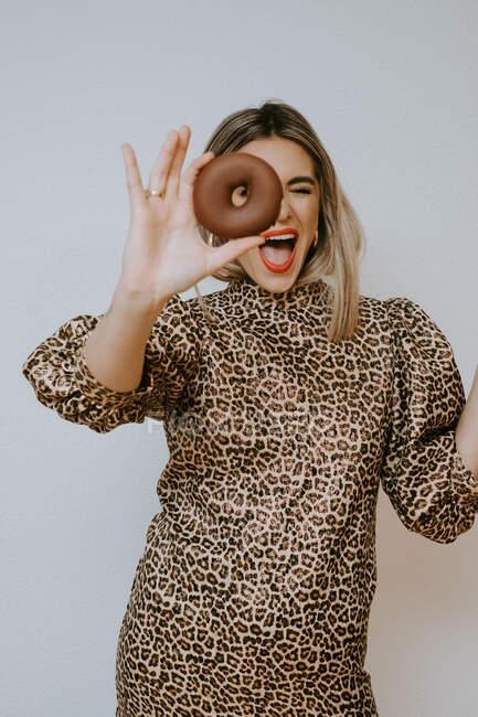 Giovane femmina in abito con leopardo stampa labbra bronzanti e guardando la fotocamera attraverso dolce ciambella al cioccolato su sfondo grigio — Foto stock