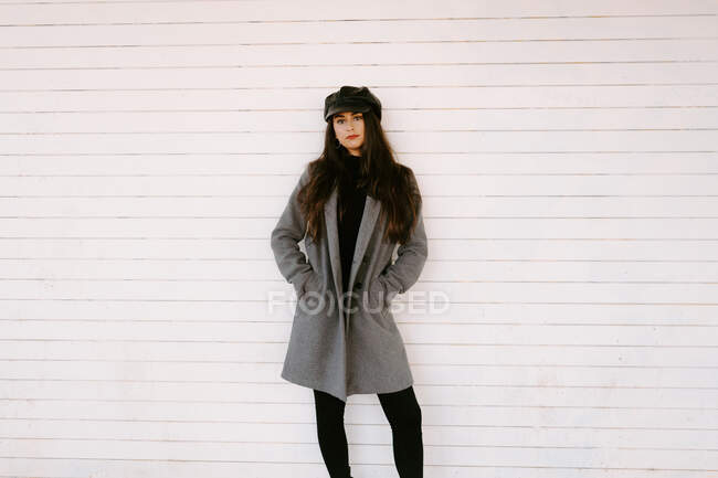 Serious young woman keeping hands in pockets of stylish coat and looking at camera against white wall on street — Stock Photo