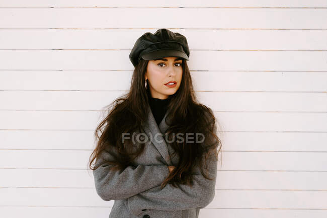 Selbstbewusste junge Frau nahe weißer Mauer — Stockfoto