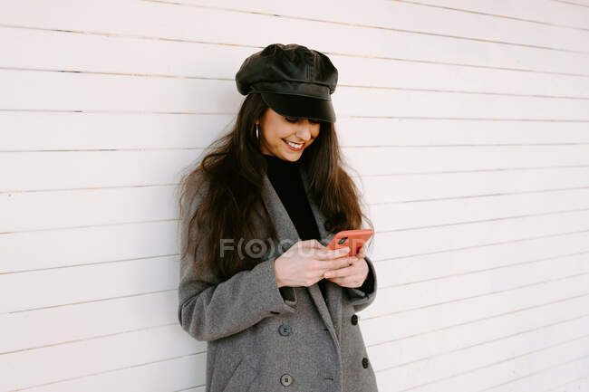 Cheerful young woman in trendy outerwear smiling and browsing smartphone while leaning on white building wall on street — Stock Photo