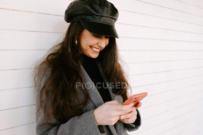 Щаслива жінка за допомогою смартфона біля стіни. — стокове фото