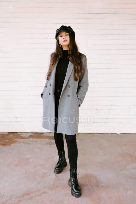 Confident young woman near white wall — Stock Photo