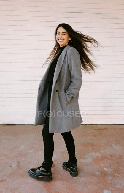 Full length excited young woman in trendy coat smiling and looking at camera over shoulder while whirling near white building on city street — Stock Photo