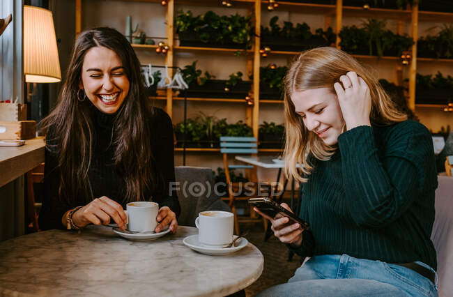 Young women laughing at joke while drinking coffee and using smartphone during meeting in cozy restaurant — Stock Photo