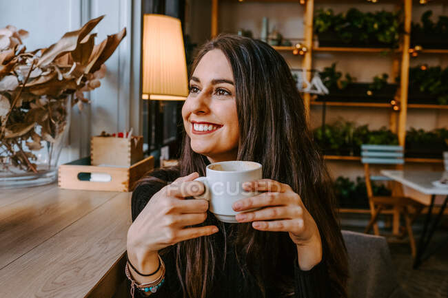 Delighted woman drinking coffee in cafe — Stock Photo